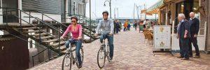Couple riding bikes on a river cruise excursion