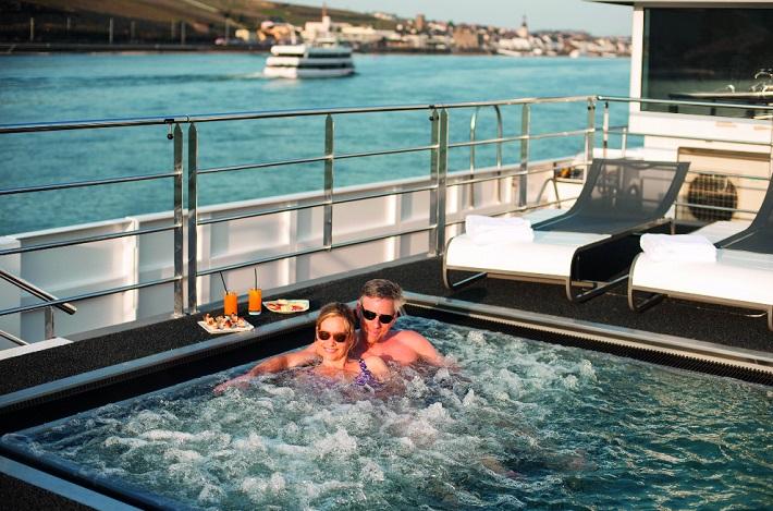 Couple bathing in Scenic Amber's sun deck vitality pool