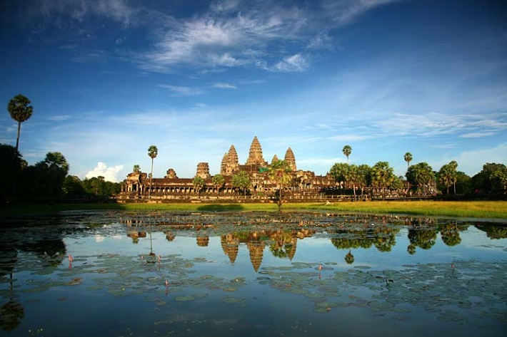 Angkor Wat seen from across a lake on a sunny day in Cambodia