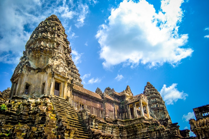 The temple spires of Angkor Wat rising up against a bright blue sky