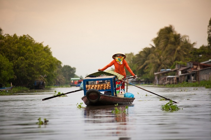 A figure paddling their boat through a Vietnamese floating market on the Mekong