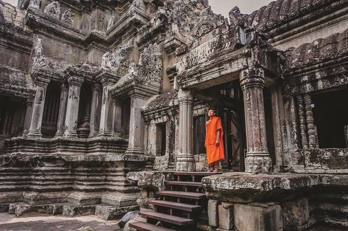 Monk standing in a temple entrance at Angkor Wat