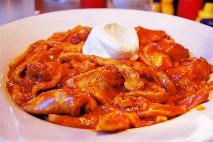 A bowl of chicken paprikash topped with Hungarian sour cream