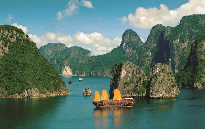 Boats sailing past cliffs in the bright blue waters of Ha Long Bay