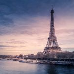 Eiffel Tower sitting next to the Seine and rising up against a pink sunrise