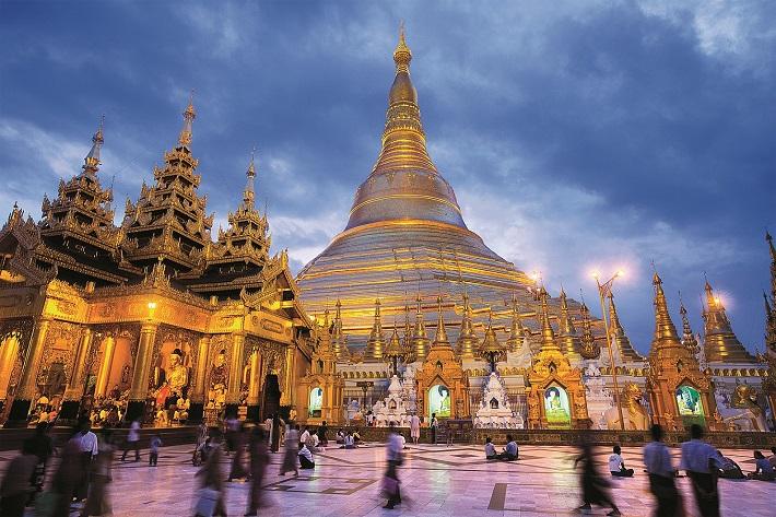 People walking around Shwedagon Pagoda at night time