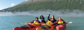Family waving to the camera from kayaks during a Tauck river cruise excursion