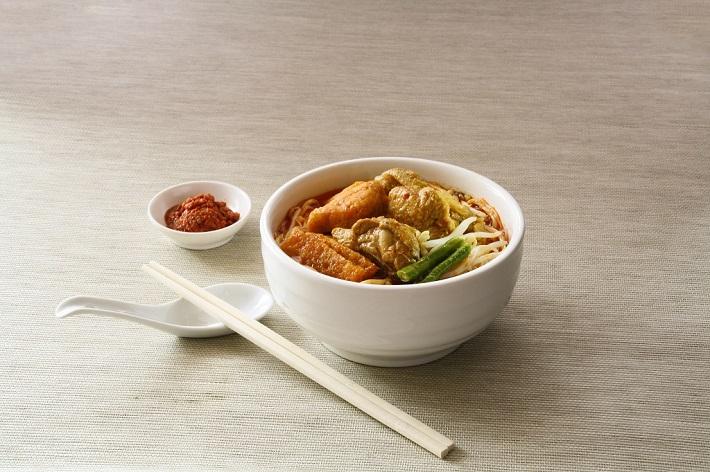 Chopsticks lying next to a bowl of Vietnamese noodle soup with dumplings
