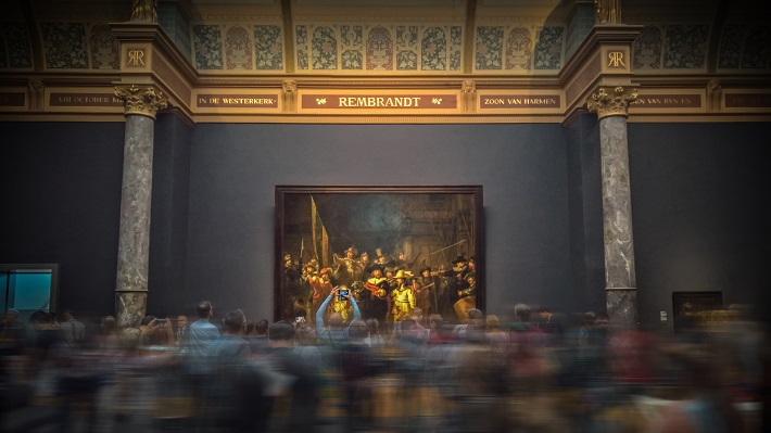 Visitors streaming past an elaborate painting in an art gallery in Amsterdam
