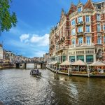 Boat sailing down a picturesque canal bordered by gabled buildings in Amsterdam