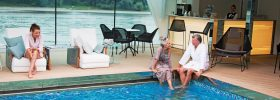 Couples relaxing in the pool area of Emerald Liberte, which transforms into a pool area at night
