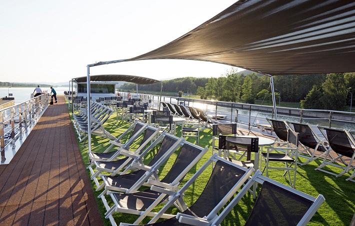 Sun shining onto the lawn and seating area on-board Emerald Liberte's sun deck