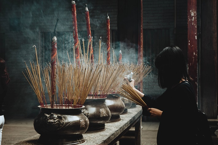 Temple visitor lighting incense sticks in Ho Chi Minh City