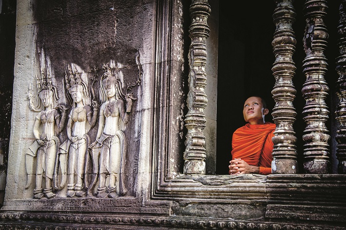A Buddhist monk looking out of a temple at Angkor Wat