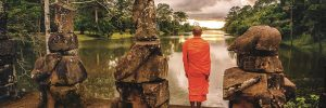 A Buddhist monk standing in temple grounds in front of the Mekong river in Cambodia