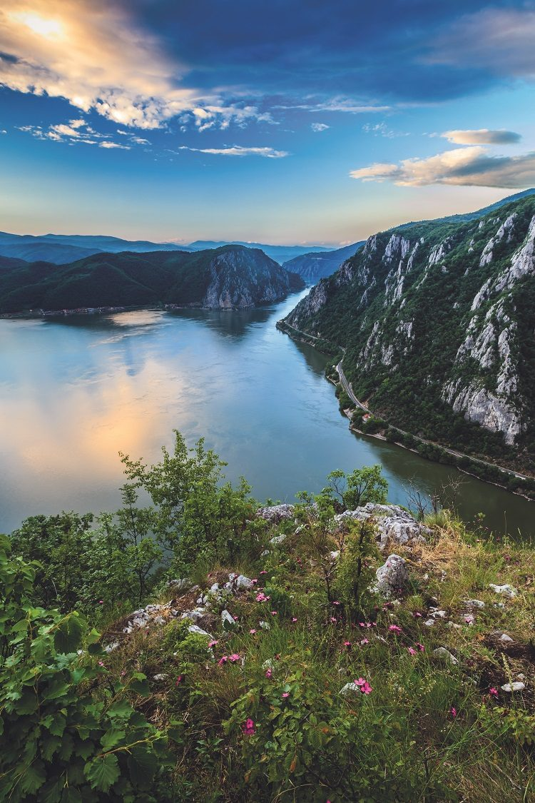 The sun rising over the lush cliffsides and still water of the Danube Gorge