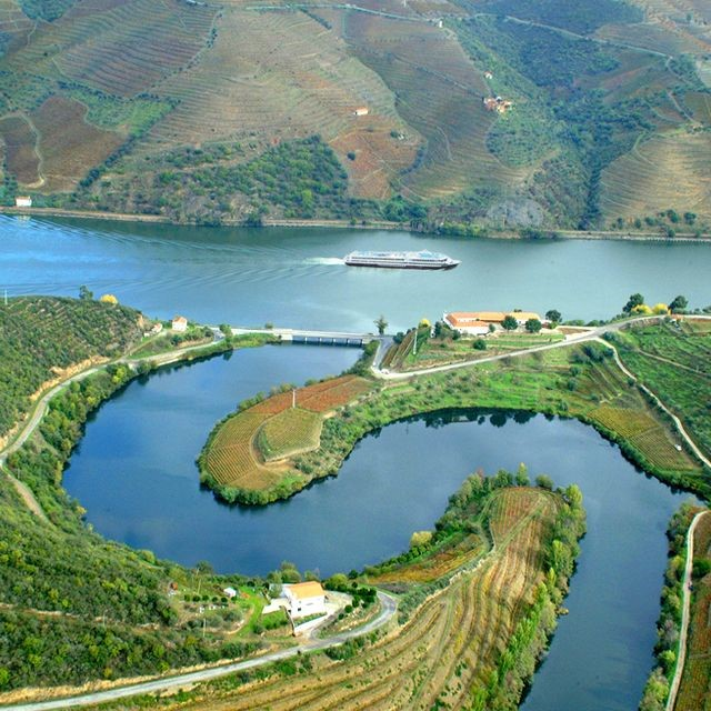 A sweeping bend in the Douro bordered by verdant fields and hillsides