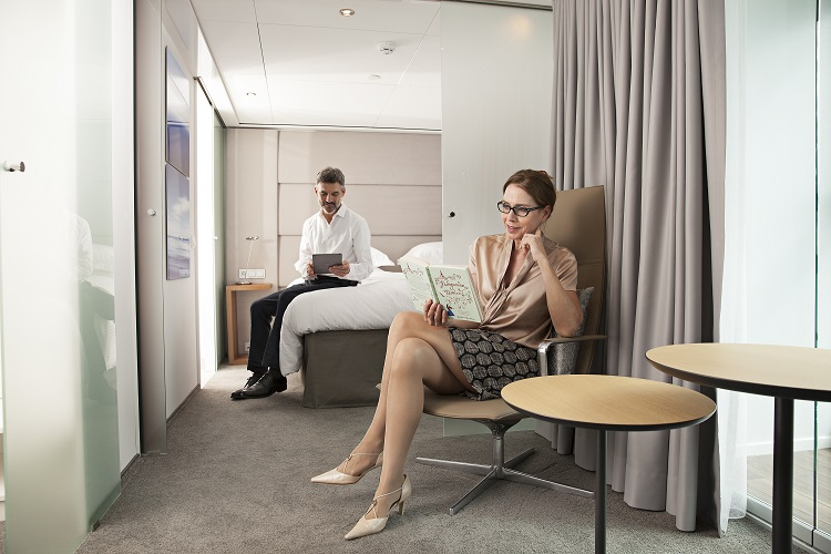 A couple reading in the lounge area of a suite on-board Emerald Radiance