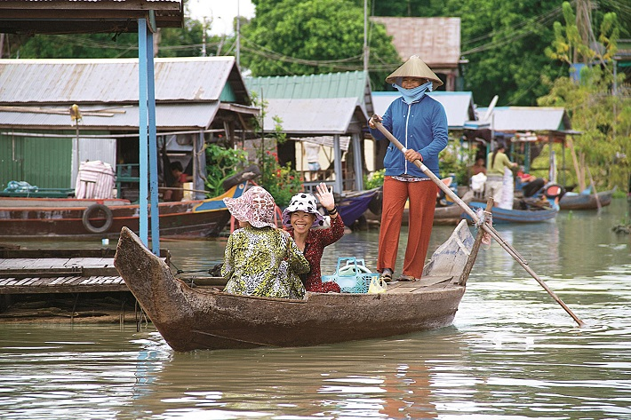 Villagers on a boat in a floating village in Vietnam