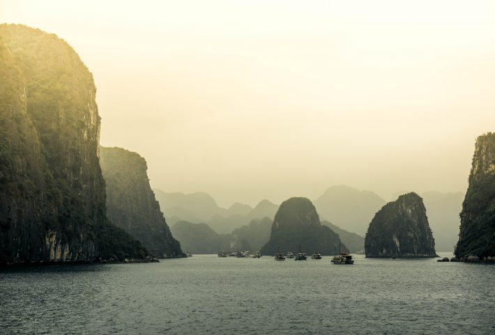 Ha Long Bay in Vietnam, as the hazy sun sets during a Mekong river cruise