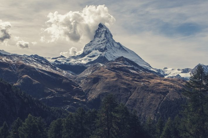 The snow-capped peak of the Matterhorn rising up to meet the clouds in Switzerland