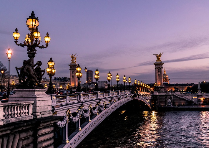 An ornate bridge, illuminated by lanterns, reaching over the Seine River at night