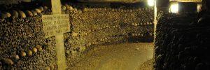 Human skulls and bones lining a corridor in the Paris catacombs