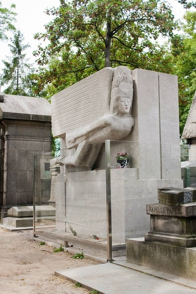 Oscar Wilde's grand grave, surrounded by glass barriers, at Pere Lachaise cemetery in Paris