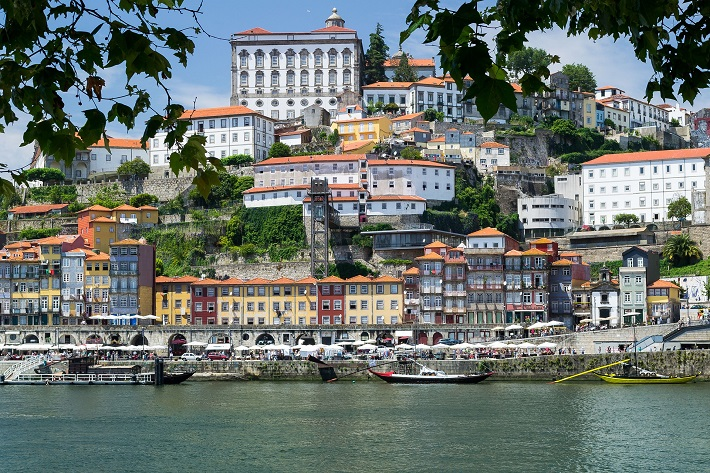 Pastel-coloured buildings lining the shores of Porto river cruise port