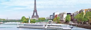 A Uniworld river cruise ship sailing down the Seine in Paris, past the Eiffel Tower