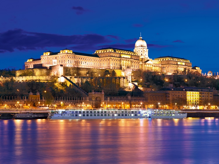 Uniworld's River Beatrice cruise ship sailing the Danube in front of an illuminated palace at night