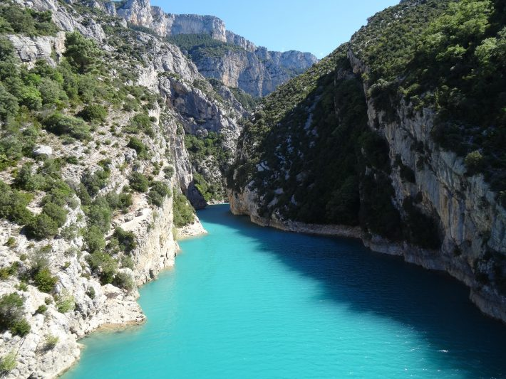 Bright blue water between lush cliffs in the Verdon Gorge in France