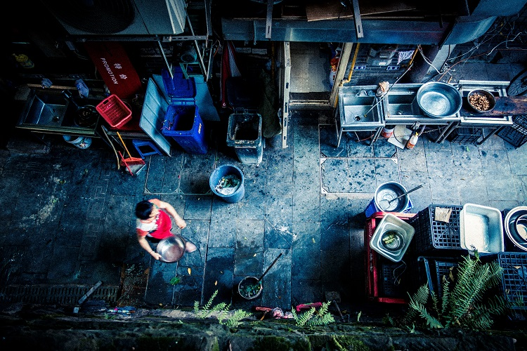 A local carrying produce down an alleyway in Chongqing, China