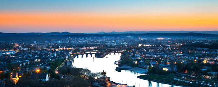 The Rhine winding through Koblenz as the sun sets at night