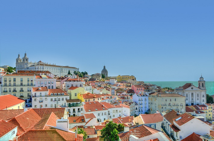 Houses with terracotta roofs leading down to the sea in Lisbon