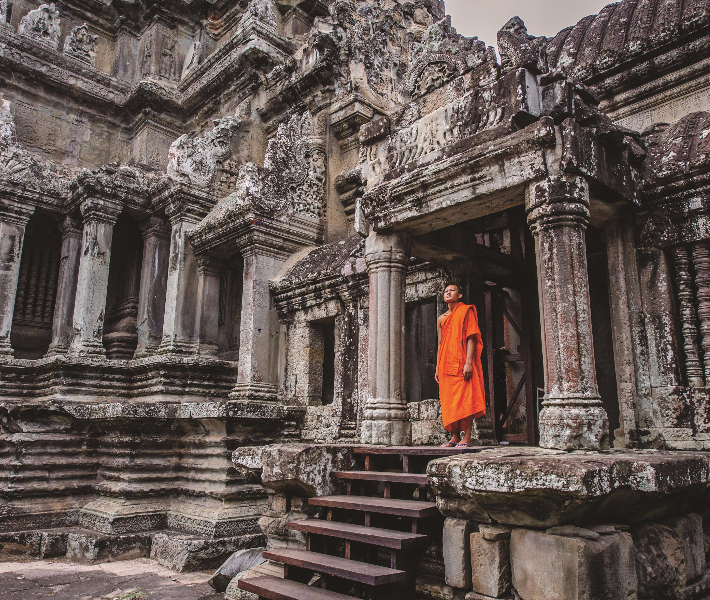 A Buddhist monk in saffron robes standing in the doorway of a temple at Angkor Wat