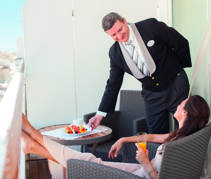 A butler serving breakfast to a passenger on a luxury river cruise
