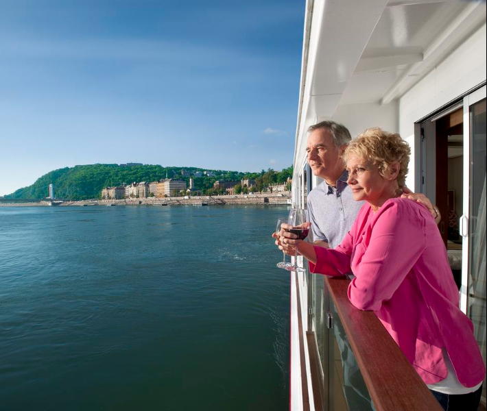 A couple enjoying a glass of wine on the veranda of their river cruise ship