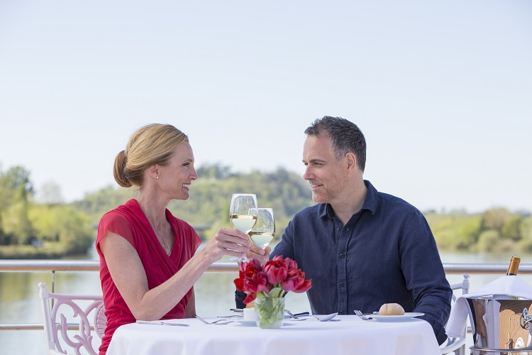 A couple toasting their holiday on the deck of a Uniworld river cruise ship