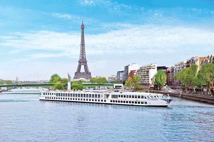 Uniworld's River Baroness cruise ship sailing past the Eiffel Tower in Paris