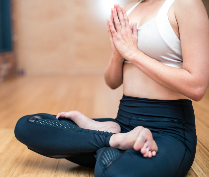 Woman sat in yoga pose - part of a wellness programme