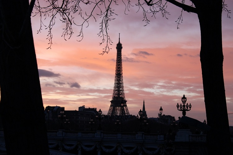 Sun setting behind the Eiffel Tower - a famous landmark of France and the Seine River