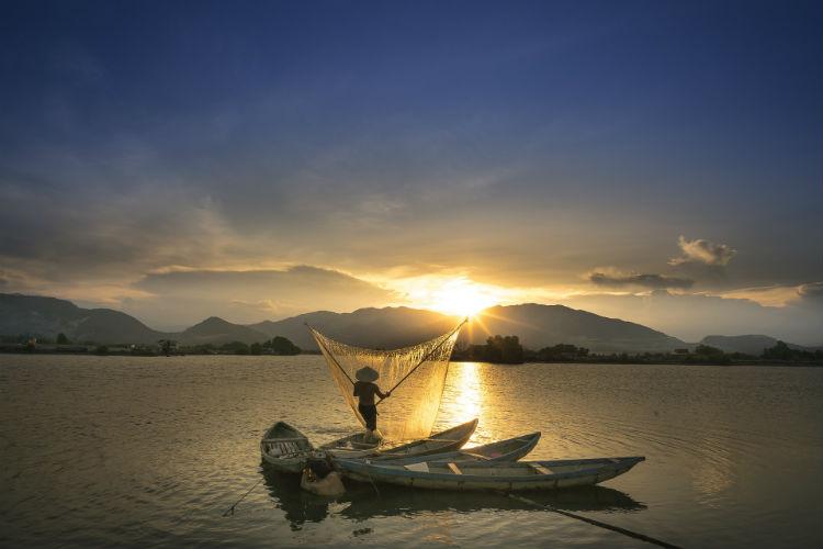 Fisherman sailing along the Mekong River