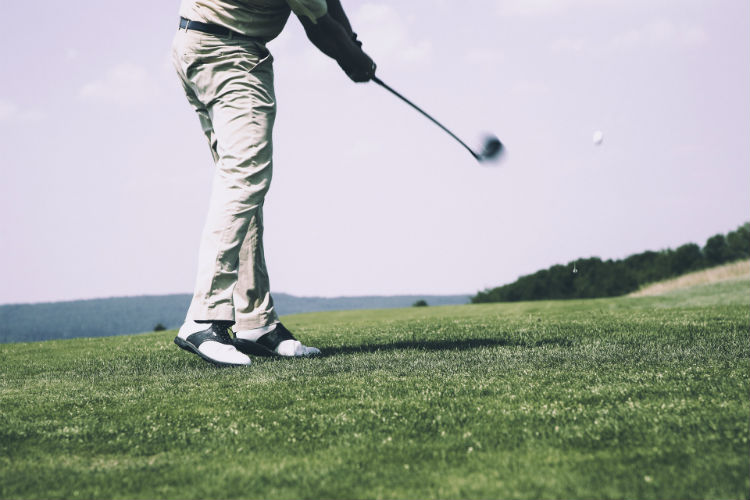 Man playing golf, mid-swing