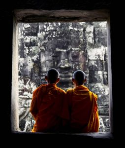 Buddhist monks sitting in a window at Angkor Wat