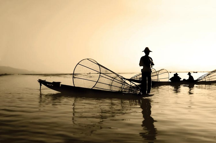 Man in a traditional fishing boat in Cambodia at sunset