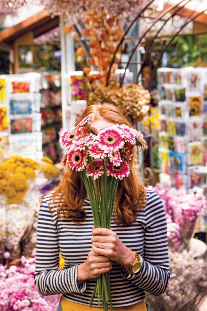 An Amsterdam river cruise passenger holding colourful flowers up in front of her face