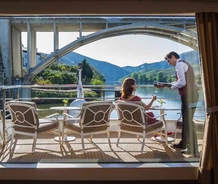 Butler serving woman on balcony of a Uniworld river cruise ship