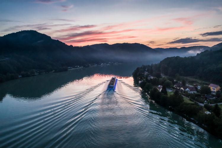 Uniworld river cruise ship sailing into the sunset